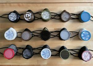 15 respirator masks in different colors and designs arranged in a grid layout on a table