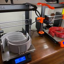 Picture of two Prusa 3D Printers with face shield components. The left most printer has a completed build plate of eight face shield headbands printed in grey filament and the printer on the right shows a completed build plate of four of the same model headband printed in red.